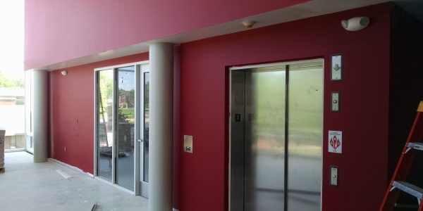 Sports complex elevators, red painted walls, white pillars