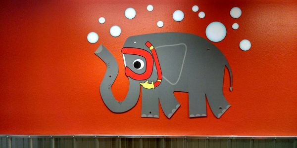 ROL Children's Wing Elephant graphic on orange wall over corrugated steel panels