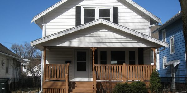 white 1.5 story exterior residential home with brown painted porch