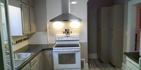 oak painted cabinets white tile backsplash, white stone and stainless venthood