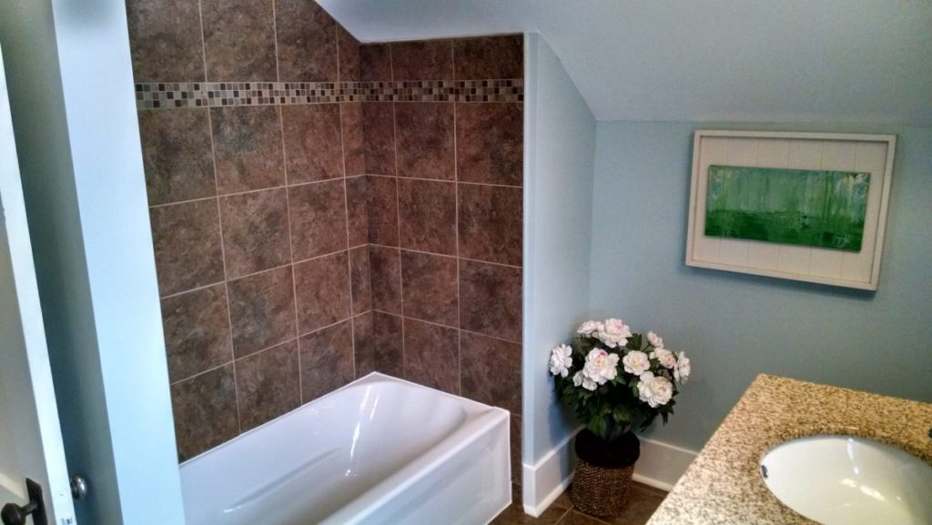 bathroom renovation with new tub brown tile shower surround, blue walls, and white trim