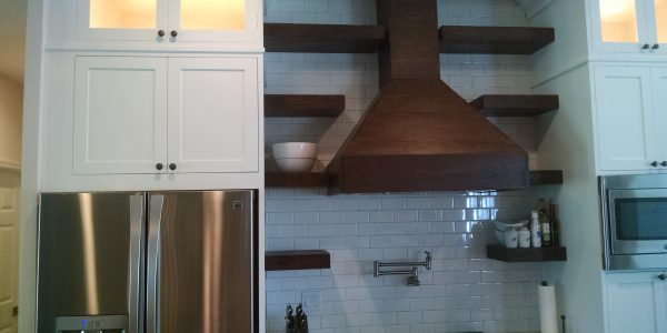 Rustic modern cabinet refinishing project with custom white cabinets and dark stained venthood