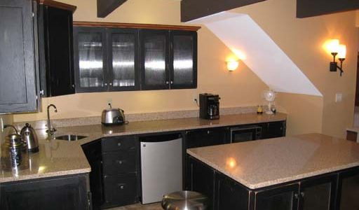 basement kitchenette with black cabinets and rustic beams