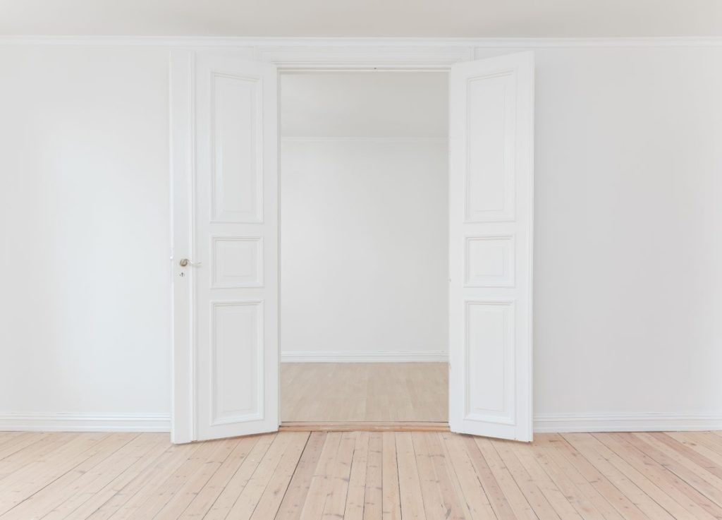 French doors open in a white room